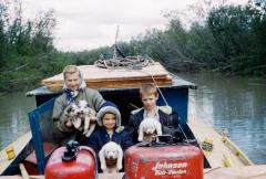 Vi, Tim, and Raymie Redington seated in a boat with four dogs (puppies).