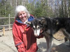 Mary Shields in her dog yard with one of her huskies.